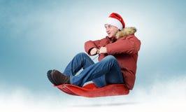 Homem no tampão vermelho Santa Claus em um pequeno trenó Foto de Stock Royalty Free