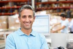 Homem no terminal de computador no armazém de distribuição Imagem de Stock