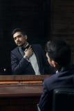 Homem no terno azul e borboleta que senta-se na cadeira que olha no espelho no barbeiro Imagens de Stock