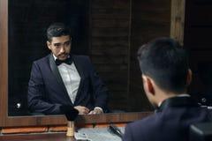 Homem no terno azul e borboleta que senta-se na cadeira que olha no espelho no barbeiro Fotos de Stock
