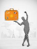 Homem no terno completo do corpo que apresenta a mala de viagem das férias Fotos de Stock Royalty Free