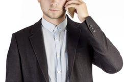 Homem no terno de negócio que chama pelo close-up do telefone isolado no fundo branco Fotos de Stock