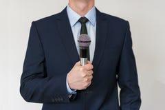 Homem no terno de negócio que guarda um microfone foto de stock