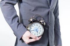 Homem no terno de negócio que guarda um pulso de disparo - no tempo e no conceito do negócio Imagens de Stock Royalty Free