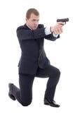 Homem no terno de negócio que senta-se no joelho e que dispara com isola da arma Fotos de Stock