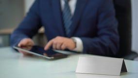 Homem no terno de negócio que trabalha no PC da tabuleta, molde vazio da placa de identificação para o texto video estoque