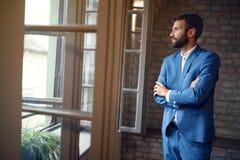 Homem no terno do homem que está perto da janela aberta Imagens de Stock