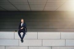 Homem no terno formal que senta-se na parede Fotos de Stock