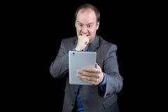 Homem no terno irritado na tabuleta Imagem de Stock Royalty Free