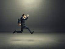 Homem no terno que corre rapidamente na sala escura Fotos de Stock