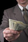 Homem no terno que dá dólares Fotos de Stock Royalty Free