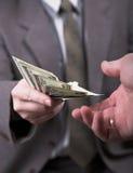 Homem no terno que dá dólares Fotografia de Stock