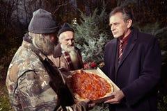 Homem no terno que dá a pizza a dois homens desabrigados no parque fotografia de stock royalty free