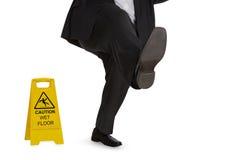 Homem no terno que desliza no assoalho molhado imagens de stock royalty free
