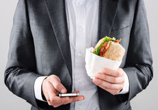 Homem no terno que envia sms ao obter o almoço Imagens de Stock Royalty Free
