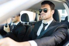 Homem no terno que fornece a segurança para dirigir During Journey imagens de stock royalty free
