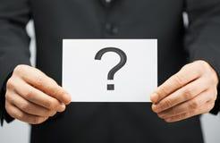 Homem no terno que guarda o cartão com ponto de interrogação Imagem de Stock