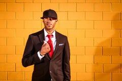 Homem no terno que guarda o revestimento pela parede amarela Imagem de Stock Royalty Free