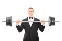 Homem no terno que guarda um barbell Imagem de Stock Royalty Free