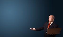 Homem no terno que guarda um portátil e que apresenta o espaço da cópia Fotografia de Stock