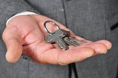 Homem no terno que mostra uma porta-chaves Fotografia de Stock Royalty Free