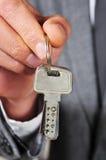 Homem no terno que mostra uma porta-chaves Fotos de Stock