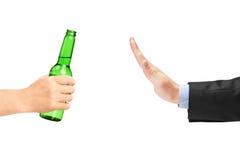 Homem no terno que recusa uma garrafa da cerveja imagem de stock