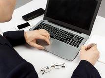 Homem no terno que senta-se com portátil Imagem de Stock