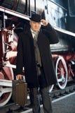 Homem no terno retro, no chapéu de jogador e na mala de viagem levantando no locomot velho Imagem de Stock