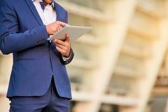 Homem no terno usando a tabuleta Fotografia de Stock Royalty Free