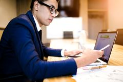 Homem no texto de datilografia do empregador bem sucedido do terno no telefone celular durante a utilização do caderno imagens de stock royalty free