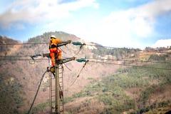 Homem no trabalho O técnico está reparando sistemas de transmissão de alta tensão nos polos de poder imagem de stock