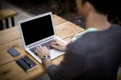 Homem no trabalho: Portátil do portátil e telefone, escritório domiciliário foto de stock royalty free