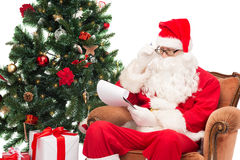 Homem no traje de Papai Noel com bloco de notas Imagens de Stock Royalty Free