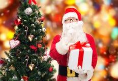 Homem no traje de Papai Noel com caixa de presente Imagem de Stock