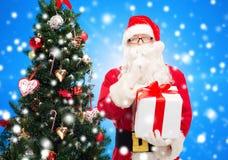 Homem no traje de Papai Noel com caixa de presente Fotografia de Stock