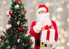 Homem no traje de Papai Noel com caixa de presente Imagens de Stock Royalty Free