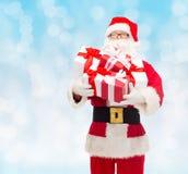 Homem no traje de Papai Noel com caixas de presente Fotos de Stock