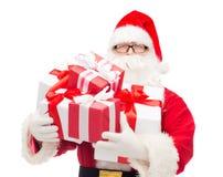 Homem no traje de Papai Noel com caixas de presente Fotografia de Stock Royalty Free