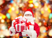 Homem no traje de Papai Noel com caixas de presente Foto de Stock