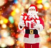 Homem no traje de Papai Noel com caixas de presente Imagens de Stock