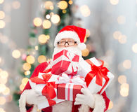 Homem no traje de Papai Noel com caixas de presente Fotos de Stock Royalty Free