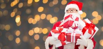 Homem no traje de Papai Noel com caixas de presente Imagem de Stock