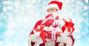 Homem no traje de Papai Noel com caixas de presente Fotografia de Stock