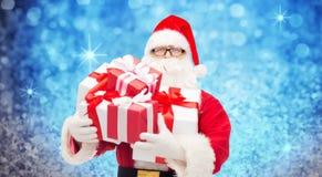Homem no traje de Papai Noel com caixas de presente Imagens de Stock Royalty Free