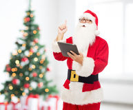 Homem no traje de Papai Noel com PC da tabuleta Fotos de Stock