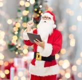 Homem no traje de Papai Noel com PC da tabuleta Imagens de Stock Royalty Free