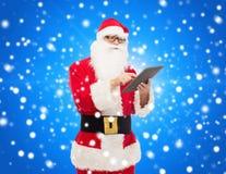 Homem no traje de Papai Noel com PC da tabuleta Imagem de Stock Royalty Free
