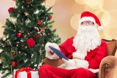 Homem no traje de Papai Noel com PC da tabuleta Fotos de Stock Royalty Free