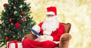 Homem no traje de Papai Noel com PC da tabuleta Foto de Stock Royalty Free